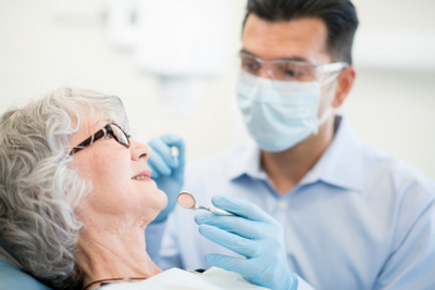 Dentist examining older patient
